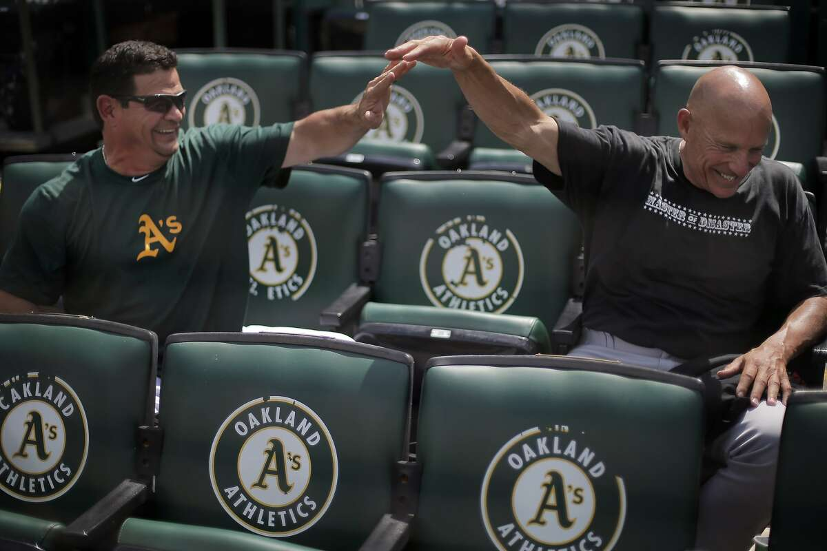 A's third base coach Mike Gallego, and Giants third base coach Tim Flannery high five during a chat at the O.co Coliseum before the game between the Giants and the A's on Monday, July 7, 2014. The two are close friends off the field, and share some successful traits in their coaching style. Both coaches were in opposing dugouts when the A's hosted the Giants.