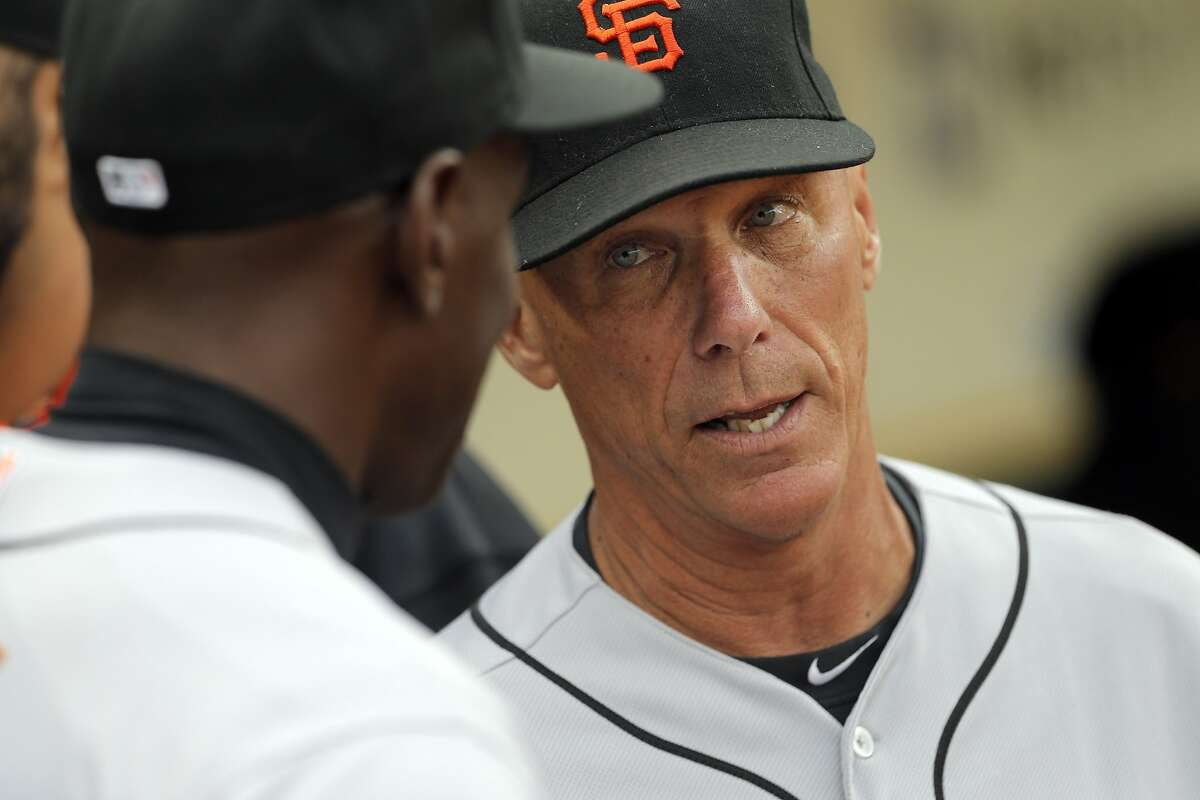 Giants third base coach Tim Flanner speaks with first base coach Roberto Kelly before the Giants' game against the Oakland A's at O.co Coliseum on Tuesday, July 11, 2014. A's third base coach Mike Gallego, and Giants third base coach Tim Flannery are close friends off the field, and share some successful traits in their coaching style. Both coaches were in opposing dugouts when the A's hosted the Giants.