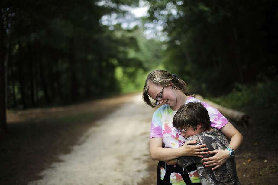 "In this July 15, 2014 photo, Liam Harrison, 13, of Nashville, Tenn., right, embraces camp worker Katie Lesesne, 21, while experiencing a tic where he feels the urge to hug someone in proximity at Camp Twitch and Shout, a camp for children with Tourette Syndrome in Winder, Ga. ""When I get the feeling, I just want to squeeze someone,"" explains Harrison. ""When I let go it makes me happy. It feels so awesome like I'm gaining something. It makes me feel a lot better."" (AP Photo/David Goldman) Photo: David Goldman, Associated Press"
