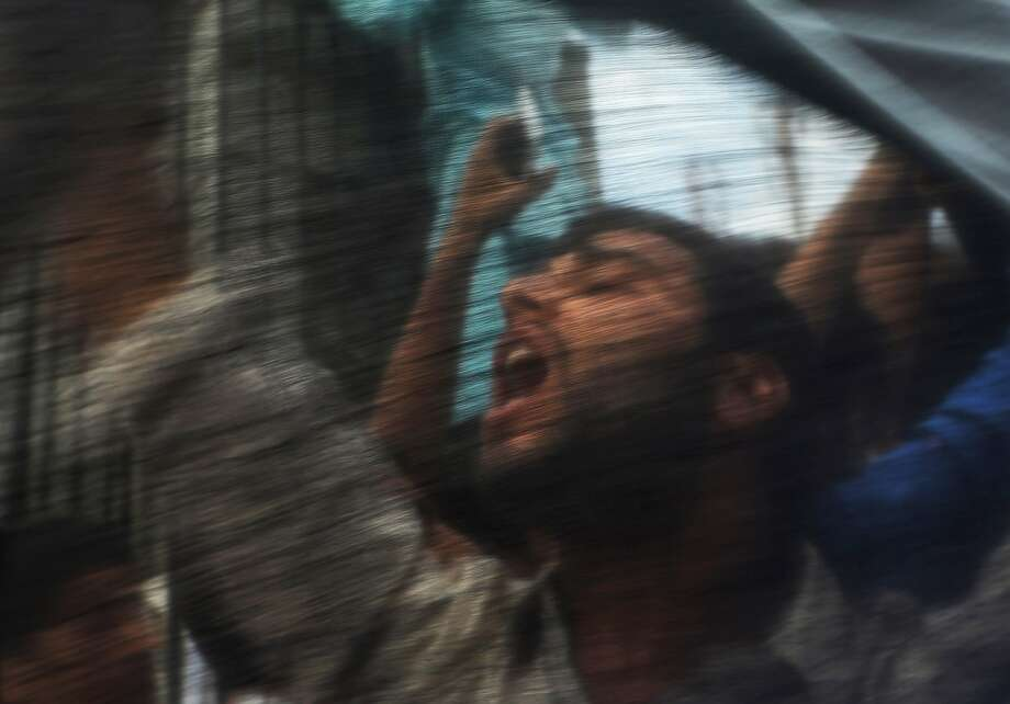 A Kashmiri Muslim protester is seen through a Palestinian flag as he shouts slogans against Israel in Srinagar, India, Friday, July. 18, 2014. Police in Indian Kashmir fired dozens of tear gas shells after violent clashes erupted after Friday prayers against Israel's attack on Gaza. (AP Photo/Dar Yasin) Photo: Dar Yasin, Associated Press