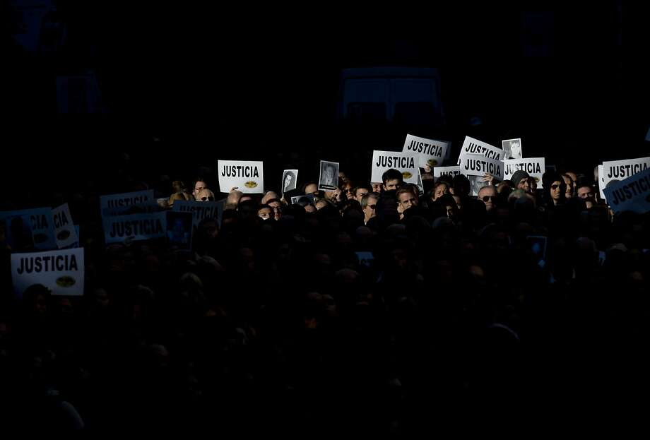 "People hold up signs that read in Spanish; ""Justice,"" and pictures of the victims of the 1994 bombing of the AMIA Jewish community center, during a commemoration ceremony in Buenos Aires, Argentina, Friday, July 18, 2014. Friday marks the 20th anniversary of the unsolved attack that left 85 dead. (AP Photo/Natacha Pisarenko) Photo: Natacha Pisarenko, Associated Press"