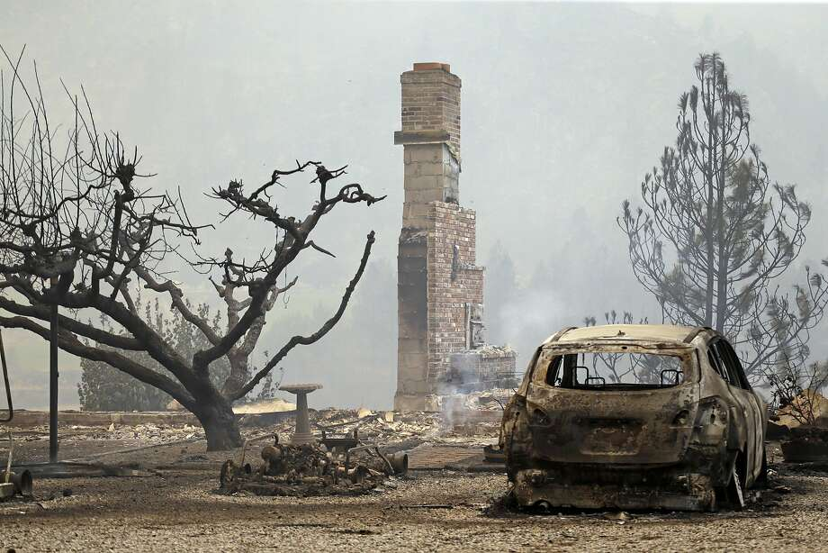 A home and a burned-out car and golf cart remain from a wildfire the night before, Friday, July 18, 2014, in Pateros, Wash. A fire racing through rural north-central Washington destroyed about 100 homes, leaving behind smoldering rubble, solitary brick chimneys and burned-out automobiles as it blackened hundreds of square miles. (AP Photo/Elaine Thompson) Photo: Elaine Thompson, Associated Press