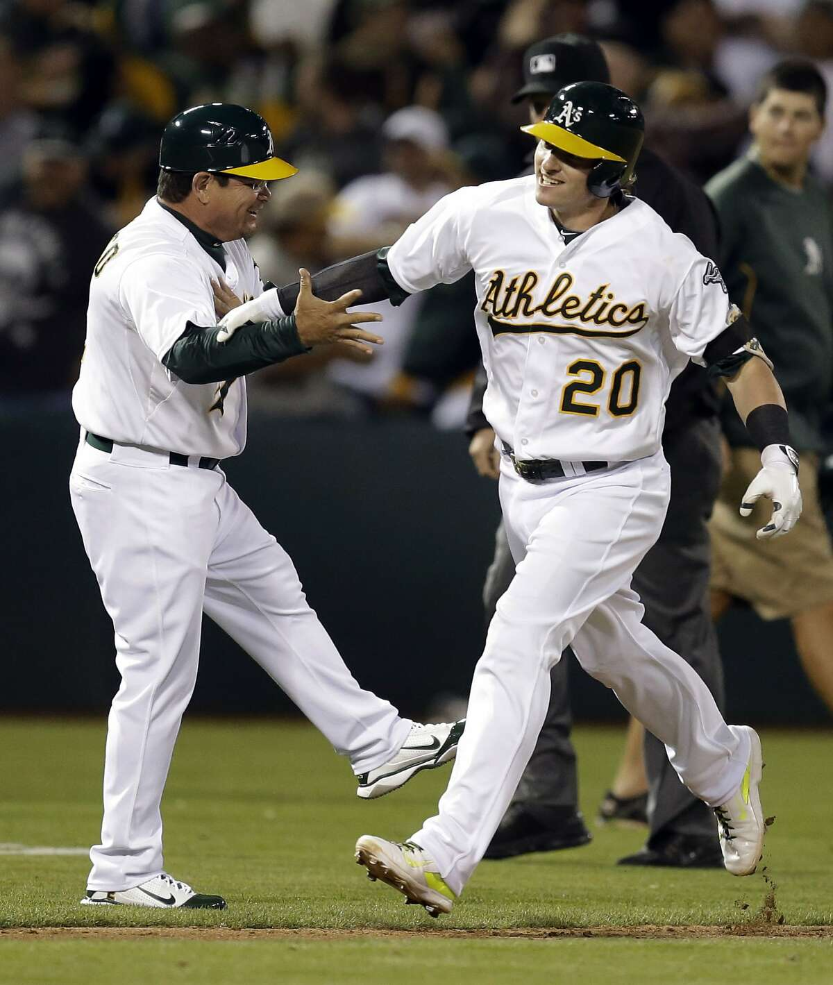 Oakland Athletics' Josh Donaldson (20) is congratulated by third base coach Mike Gallego, left, after Donaldson hit the game-winning three-run home run off Baltimore Orioles' Zach Britton in the ninth inning of a baseball game Friday, July 18, 2014, in Oakland, Calif. Oakland won 5-4. (AP Photo/Ben Margot)