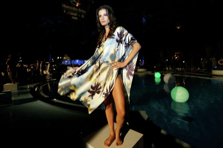 A model poses poolside wearing a swimsuit cover-up designed by Suboo during an opening party for the Mercedes-Benz Fashion Week Swim, Thursday, July 17, 2014, in Miami Beach, Fla. The event is celebrating its 10th year. Photo: Lynne Sladky, AP / AP