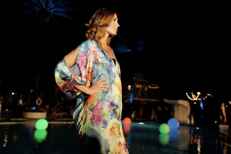A model poses poolside wearing a swimsuit cover-up designed by Beach Bunny during an opening party for the Mercedes-Benz Fashion Week Swim, Thursday, July 17, 2014, in Miami Beach, Fla. The event is celebrating its 10th year. Photo: Lynne Sladky, AP / AP