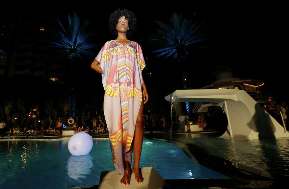 A model poses poolside wearing a swimsuit cover-up designed by Mara Hoffman during an opening party for the Mercedes-Benz Fashion Week Swim, Thursday, July 17, 2014, in Miami Beach, Fla. The event is celebrating its 10th year. Photo: Lynne Sladky, AP / AP