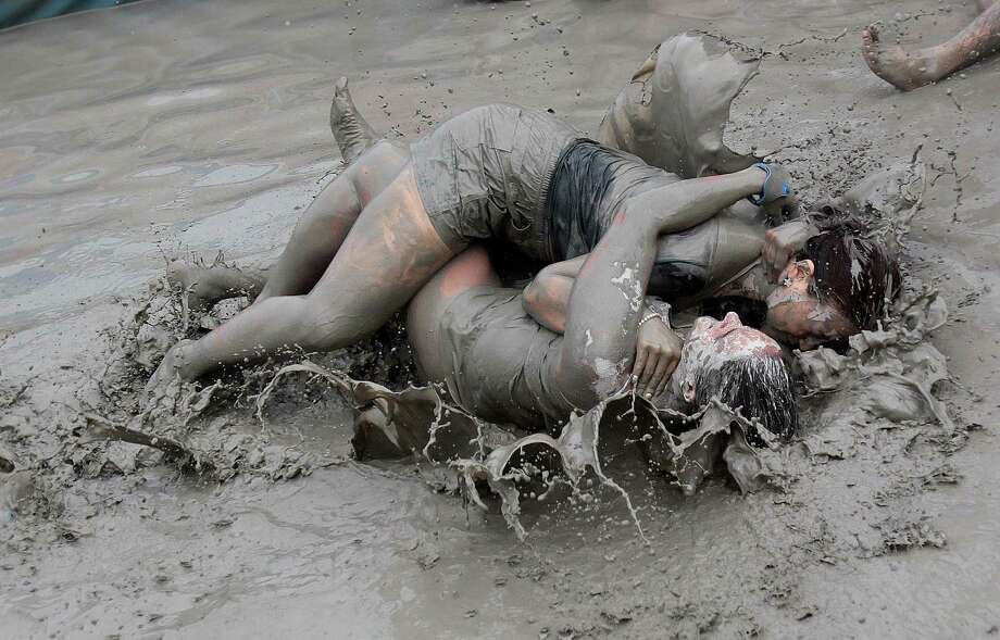 Women wrestle in a mud pool during the Boryeong Mud Festival at Daecheon Beach in Boryeong , South Korea, Friday, July 18, 2014. Photo: Ahn Young-joon, Associated Press / AP