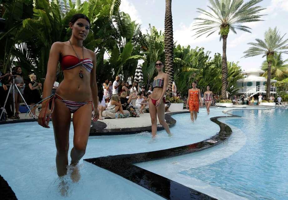 Models walk in a pool wearing swimwear designed by Poko Pano during the Mercedes-Benz Fashion Week Swim show, Friday, July 18, 2014, in Miami Beach, Fla. Photo: Lynne Sladky, AP / AP
