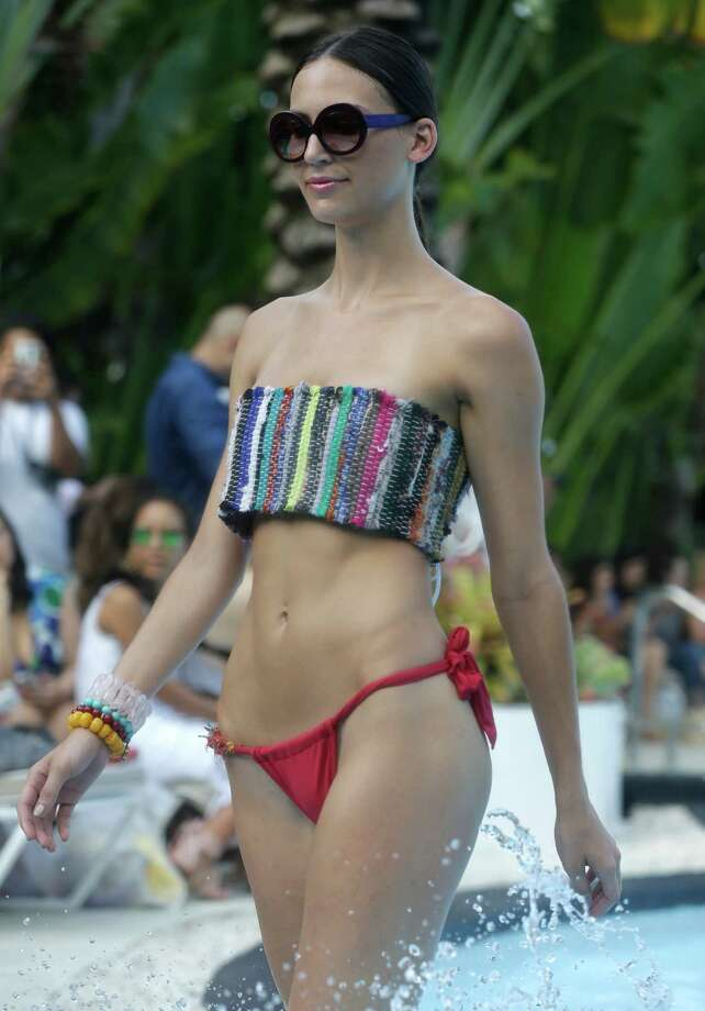 A model walks in a pool wearing swimwear designed by Poko Pano during the Mercedes-Benz Fashion Week Swim show, Friday, July 18, 2014, in Miami Beach, Fla. Photo: Lynne Sladky, AP / AP