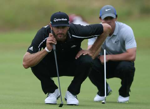 Dustin Johnson of the US, left, looks at his putt on the 15th green with Rory McIlroy of Northern Ireland at right during the third day of the British Open Golf championship at the Royal Liverpool golf club, Hoylake, England, Saturday July 19, 2014. (AP Photo/Jon Super) Photo: Jon Super, Associated Press / AP