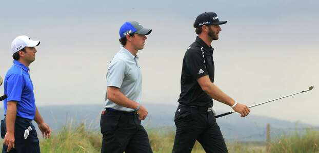 Dustin Johnson of the US, right, Rory McIlroy of Northern Ireland, center, and Francesco Molinari of Italy walk up to the 11th tee box during the third day of the British Open Golf championship at the Royal Liverpool golf club, Hoylake, England, Saturday July 19, 2014. (AP Photo/Jon Super) Photo: Jon Super, Associated Press / AP