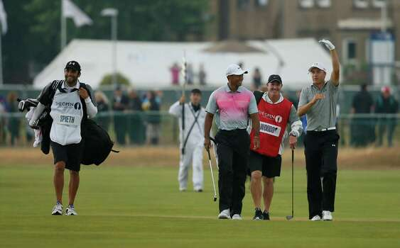 Tiger Woods of the US, center, and Jordan Spieth of the US, right, talk together as they walk along the 18th fairway with during the third day of the British Open Golf championship at the Royal Liverpool golf club, Hoylake, England, Saturday July 19, 2014. (AP Photo/Alastair Grant) Photo: Alastair Grant, Associated Press / AP