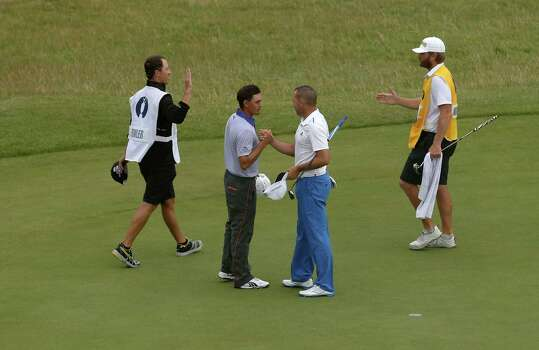 Rickie Fowler of the US, second left, shakes hands with Sergio Garcia of Spain on the 18th green at the end of their match on the third day of the British Open Golf championship at the Royal Liverpool golf club, Hoylake, England, Saturday July 19, 2014. (AP Photo/Peter Morrison) Photo: Peter Morrison, Associated Press / AP