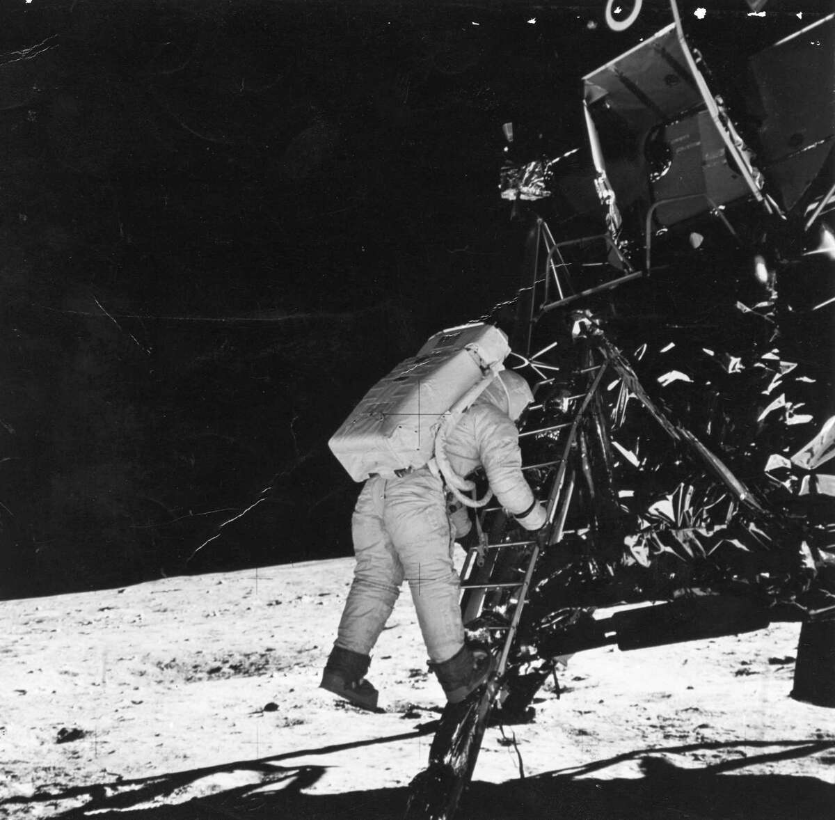 """Astronaut Edwin """"Buzz"""" Aldrin, lunar module pilot, descends the steps as he prepares to walk on the moon in 1969. The photo was made by fellow astronaut Neil Armstrong."""