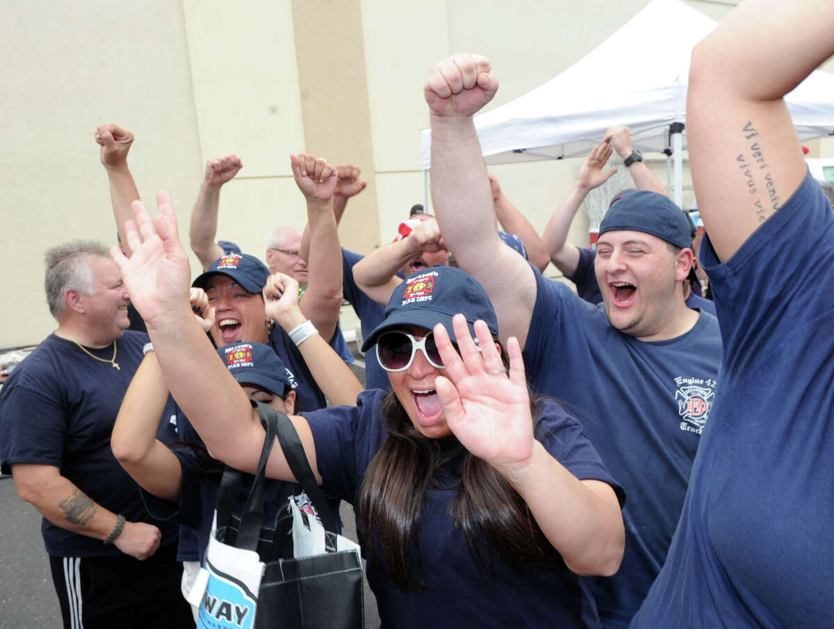 Belltown fire fighter, Zack LaMotta, right, and other members of the Belltown Fire Department react after their department was declared the winner of Stamford Firefighter Cook-Off at Fairway Market in Stamford, Conn., Saturday afternoon, July 19, 2014.