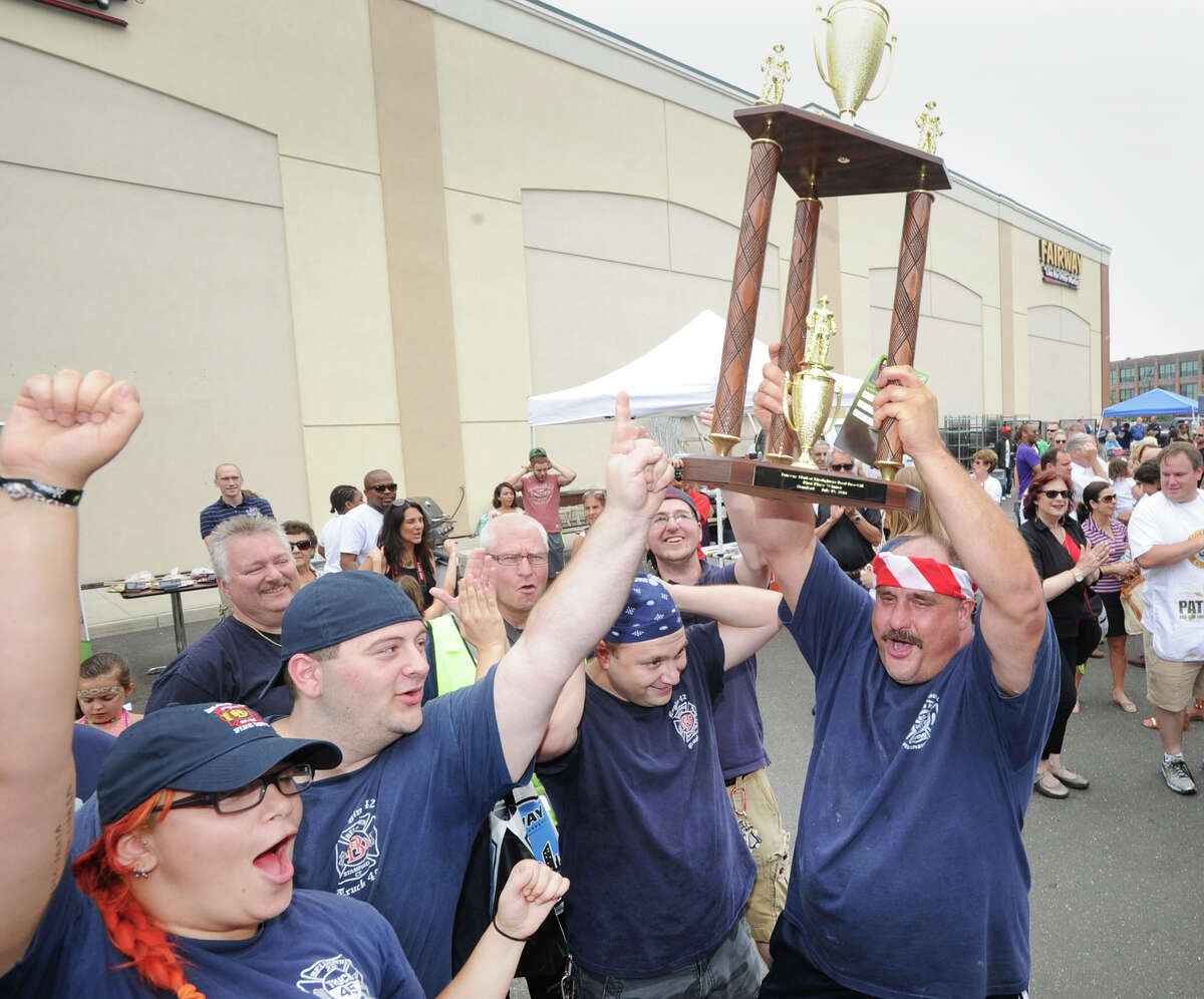 At right, Peter Cogliano of the Belltown Fire Department, holds the first place trophy above his head while surrounded by fellow Belltown fire fighters at the conclusion of the Stamford Firefighter Cook-Off at Fairway Market in Stamford, Conn., Saturday afternoon, July 19, 2014.