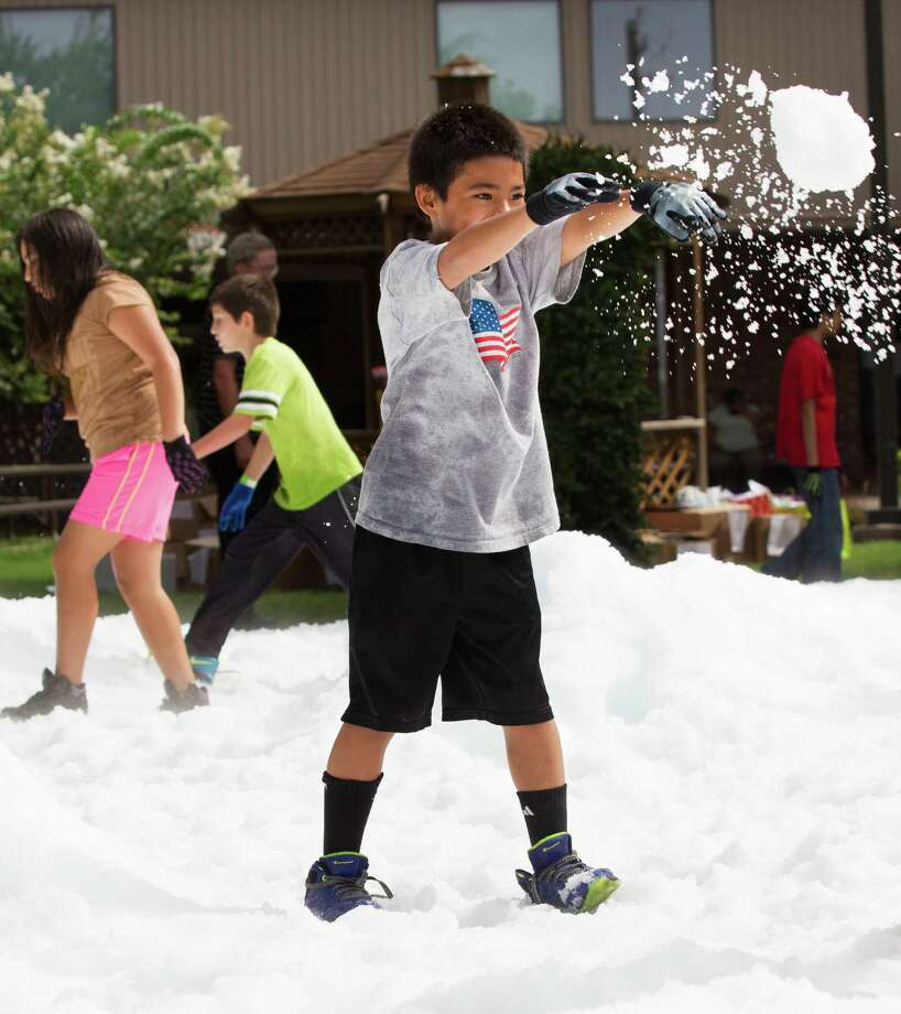 George Dominguez throws a snowball during a Christmas in July celebration for the more than 70 homeless children to play in at the Star of Hope Transitional Living Center Saturday, July 19, 2014, in Houston. About 800 pounds of snow was created and distributed over a 45-foot area on mission's campus for the party, presented by the staff and family of Houston's TLC Office Systems. Santa also made an appearance hearing early Christmas wishes and passing out gifts as well. Photo: Brett Coomer, Houston Chronicle / © 2014 Houston Chronicle