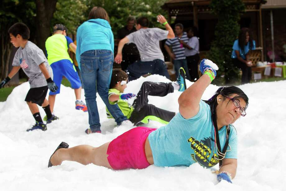 Beatrice Martinez throws a snowball during a Christmas in July celebration for the more than 70 homeless children and their families to play in at the Star of Hope Transitional Living Center Saturday, July 19, 2014, in Houston. About 800 pounds of snow was created and distributed over a 45-foot area on mission's campus for the party, presented by the staff and family of Houston's TLC Office Systems. Santa also made an appearance hearing early Christmas wishes and passing out gifts as well. Photo: Brett Coomer, Houston Chronicle / © 2014 Houston Chronicle