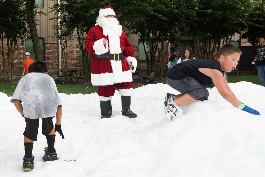 Santa walks through a pile of snow during a Christmas in July celebration for the more than 70 homeless children to play in at the Star of Hope Transitional Living Center Saturday, July 19, 2014, in Houston. About 800 pounds of snow was created and distributed over a 45-foot area on mission's campus for the party, presented by the staff and family of Houston's TLC Office Systems. Santa heard early Christmas wishes and passed out gifts as well. Photo: Brett Coomer, Houston Chronicle / © 2014 Houston Chronicle