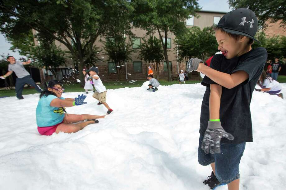 Myka Braxton, right, throws a snowball at Beatrice Martinez during a Christmas in July celebration for the more than 70 homeless children to play in at the Star of Hope Transitional Living Center Saturday, July 19, 2014, in Houston. About 800 pounds of snow was created and distributed over a 45-foot area on mission's campus for the party, presented by the staff and family of Houston's TLC Office Systems. Santa also made an appearance hearing early Christmas wishes and passing out gifts as well. Photo: Brett Coomer, Houston Chronicle / © 2014 Houston Chronicle