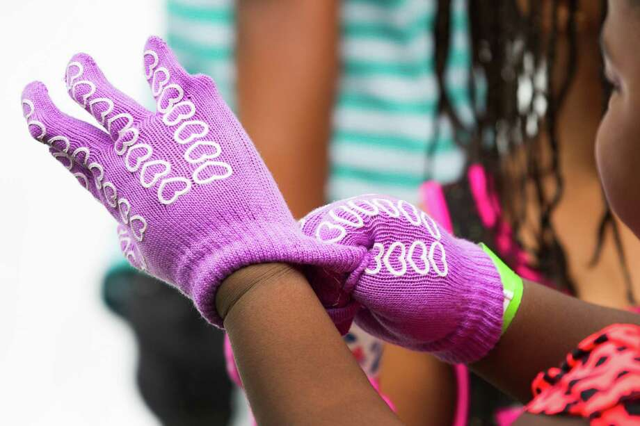 A girl puts on a pair of gloves during a Christmas in July celebration for the more than 70 homeless children to play in at the Star of Hope Transitional Living Center Saturday, July 19, 2014, in Houston. Photo: Brett Coomer, Houston Chronicle / © 2014 Houston Chronicle