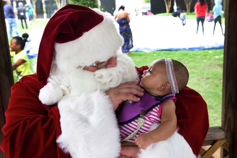 Santa holds McKayla Williamson during a Christmas in July celebration for the more than 70 homeless children to play in at the Star of Hope Transitional Living Center Saturday, July 19, 2014, in Houston. About 800 pounds of snow was created and distributed over a 45-foot area on mission's campus for the party, presented by the staff and family of Houston's TLC Office Systems. Santa also made an appearance hearing early Christmas wishes and passing out gifts as well. Photo: Brett Coomer, Houston Chronicle / © 2014 Houston Chronicle