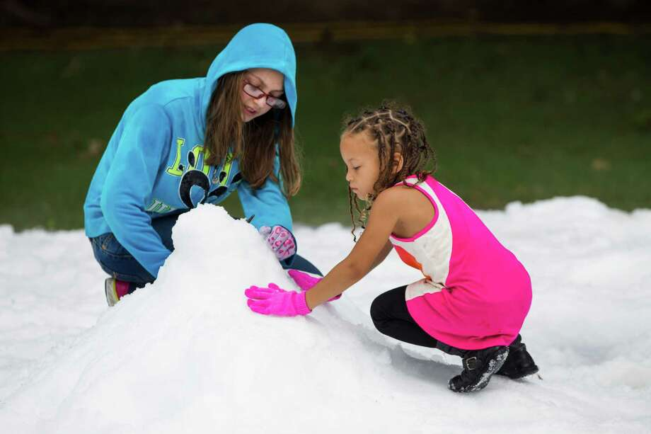 Chloe Bergeron, left, and Amia Willis build a snowman during a Christmas in July celebration for the more than 70 homeless children to play in at the Star of Hope Transitional Living Center Saturday, July 19, 2014, in Houston. About 800 pounds of snow was created and distributed over a 45-foot area on mission's campus for the party, presented by the staff and family of Houston's TLC Office Systems. Santa also made an appearance hearing early Christmas wishes and passing out gifts as well. Photo: Brett Coomer, Houston Chronicle / © 2014 Houston Chronicle