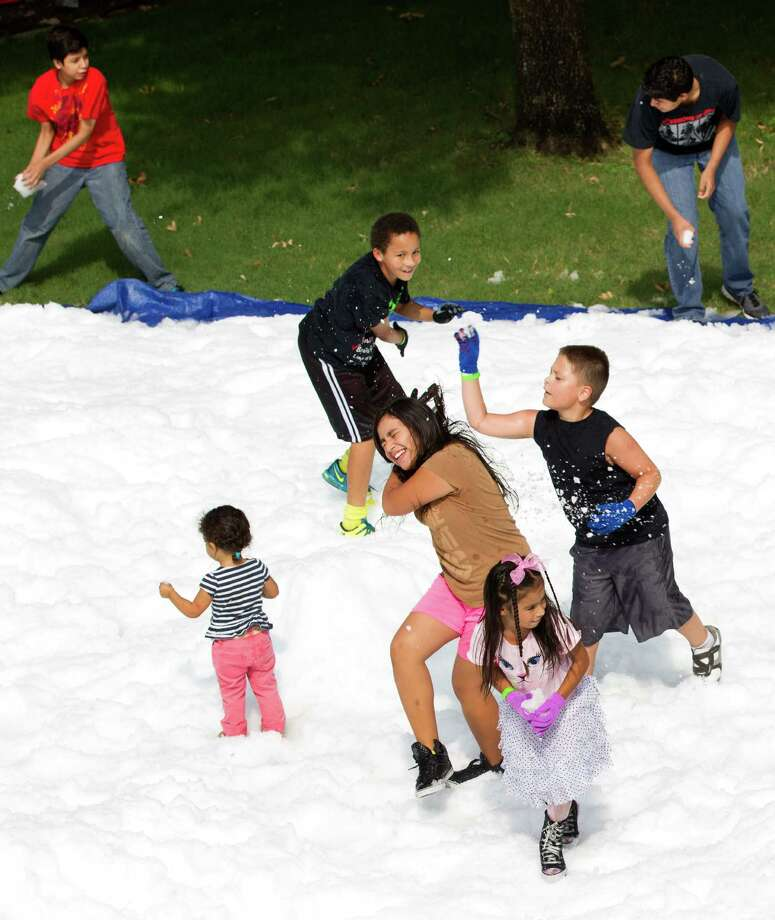 Children play in the snow during a Christmas in July celebration at the Star of Hope Transitional Living Center Saturday, July 19, 2014, in Houston. About 800 pounds of snow was created and distributed over a 45-foot area on mission's campus for the party, presented by the staff and family of Houston's TLC Office Systems. Santa also made an appearance hearing early Christmas wishes and passing out gifts as well. Photo: Brett Coomer, Houston Chronicle / © 2014 Houston Chronicle