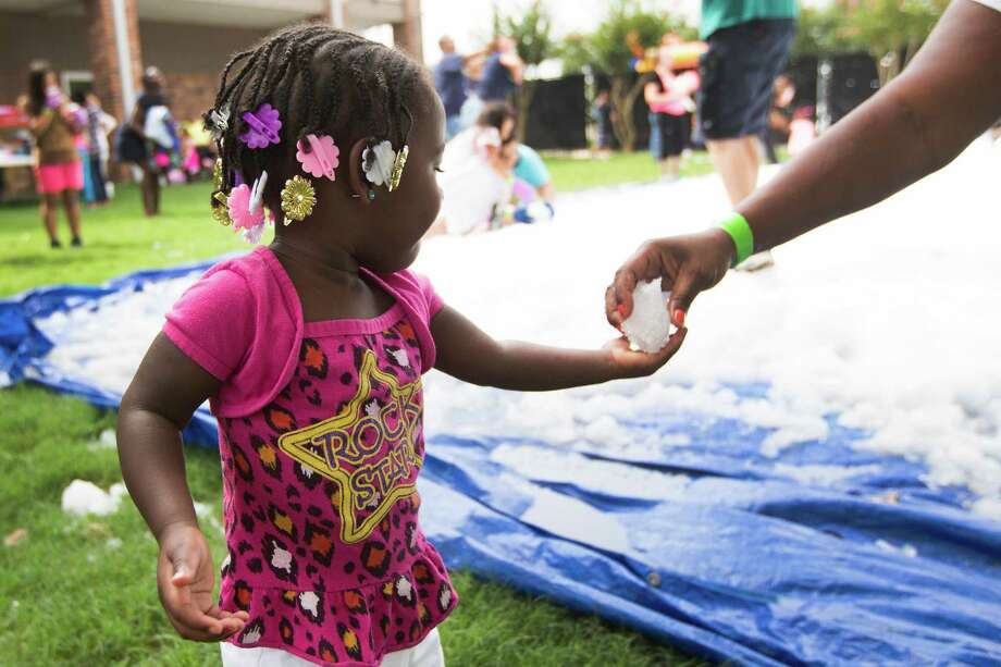 Kennedi George is handed a snowball by her mother, Inga Hypolite during a Christmas in July celebration for the more than 70 homeless children to play in at the Star of Hope Transitional Living Center Saturday, July 19, 2014, in Houston. About 800 pounds of snow was created and distributed over a 45-foot area on mission's campus for the party, presented by the staff and family of Houston's TLC Office Systems. Santa also made an appearance hearing early Christmas wishes and passing out gifts as well. Photo: Brett Coomer, Houston Chronicle / © 2014 Houston Chronicle