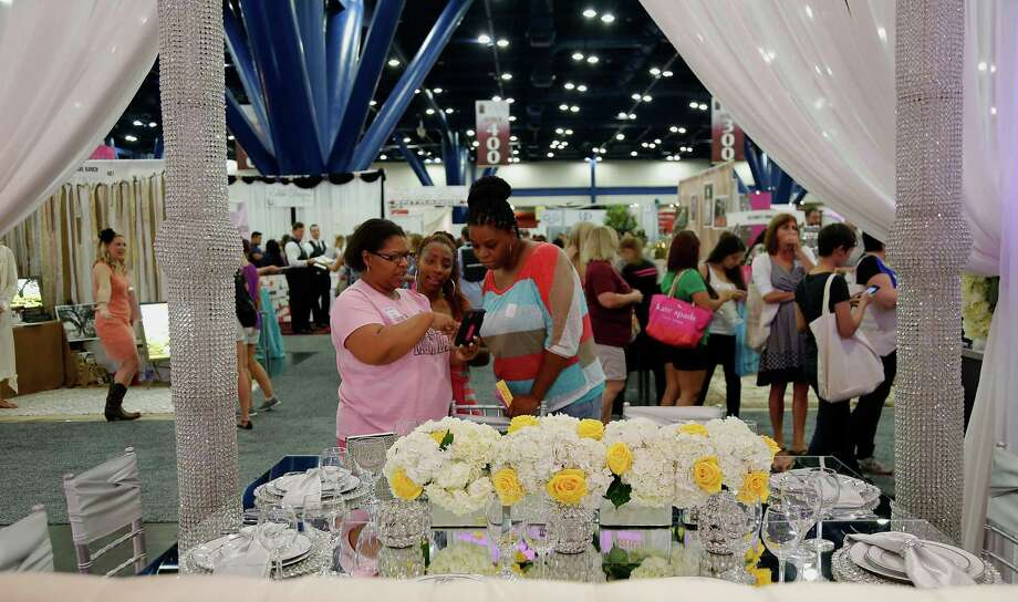 Bride to be Chantell Golmore left, her matron of honor Charity James center, and best bridesmaid Jacynth Smith right, look over a booth during the 30th Bi-Annual Bridal Extravaganza Show at the George R. Brown Convention Center. Photo: James Nielsen, Houston Chronicle / © 2014  Houston Chronicle