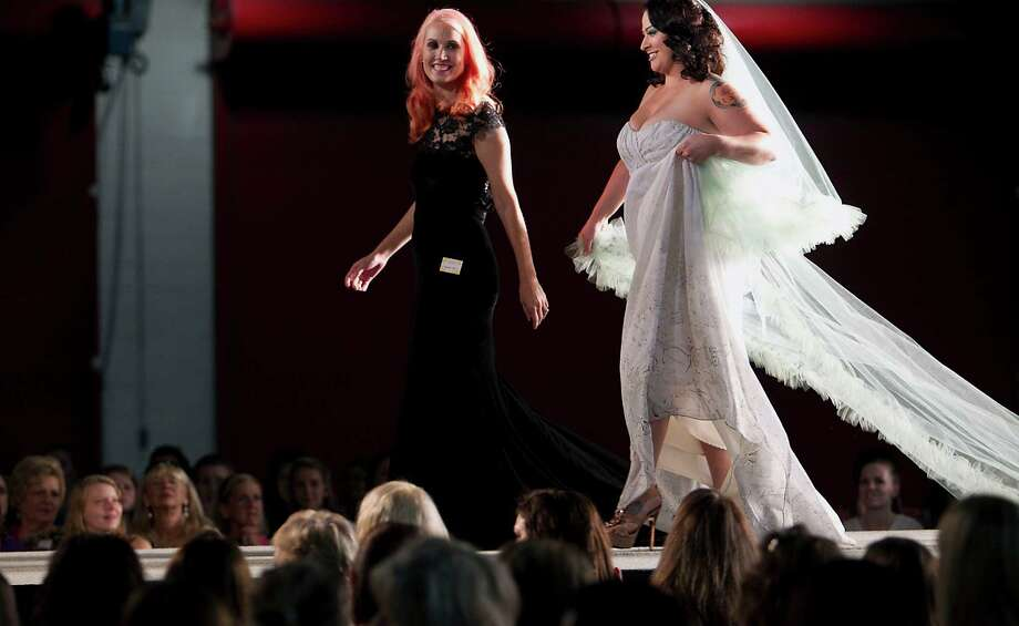 Damsel White Label designer Natalie Harris left, walks with a model on the runway after the Damsel White Label bridal fashion show at the 30th Bi-Annual Bridal Extravaganza Show at the George R. Brown Convention Center. Photo: James Nielsen, Houston Chronicle / © 2014  Houston Chronicle