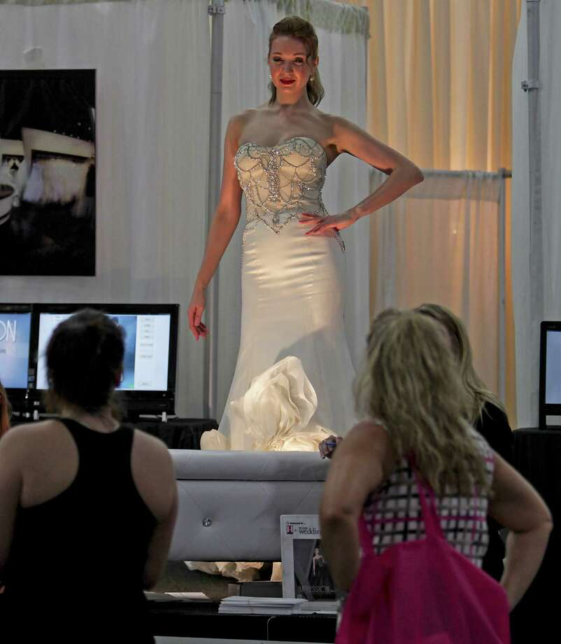 A model wears a wedding gown at the Impression Bridal booth during the 30th Bi-Annual Bridal Extravaganza Show at the George R. Brown Convention Center. Photo: James Nielsen, Houston Chronicle / © 2014  Houston Chronicle
