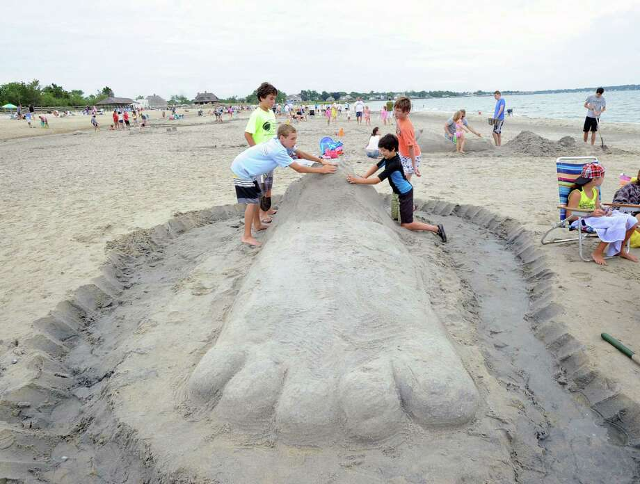 Clockwise from left, Martin Curley, 13, Carl Cummings, 12, Carl's brother, Robert, 12, and Kenzo Otsuka, 12, all of Greenwich, put the finishing touches on a big sand food sculpture they created during the Greenwich Arts Council and the Town of Greenwich Department of Parks and Recreation's Sandblast Sand Sculpture Festival at Greenwich Point, Saturday afternoon, July 19, 2014. Photo: Bob Luckey / Greenwich Time