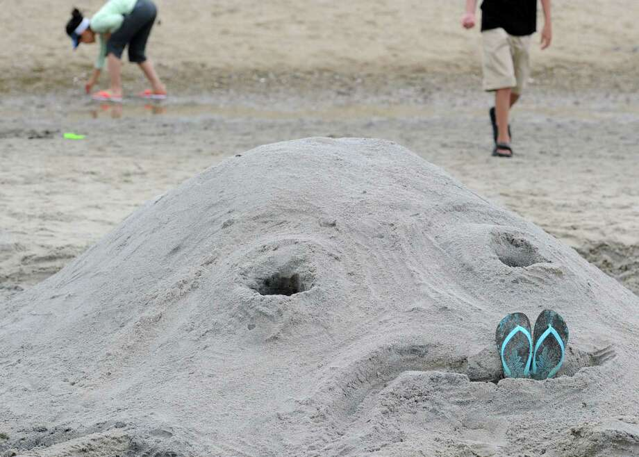 Maggie Wu of Arizona added the flip-flops in the mouth of the Liu family sand sclupture of an octopus during the Greenwich Arts Council and the Town of Greenwich Department of Parks and Recreation's Sandblast Sand Sculpture Festival at Greenwich Point, Saturday afternoon, July 19, 2014. Photo: Bob Luckey / Greenwich Time