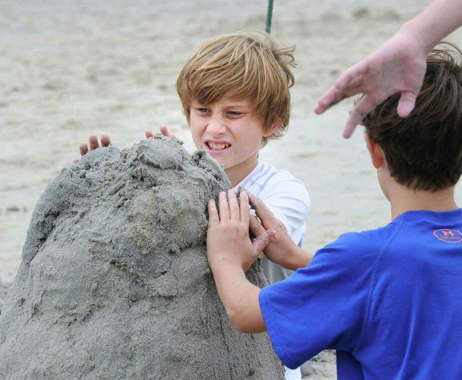 Connor Skowron, 13, of Greenwich, and friends, construct a sand castle during the Greenwich Arts Council and the Town of Greenwich Department of Parks and Recreation's Sandblast Sand Sculpture Festival at Greenwich Point, Saturday afternoon, July 19, 2014. Photo: Bob Luckey / Greenwich Time