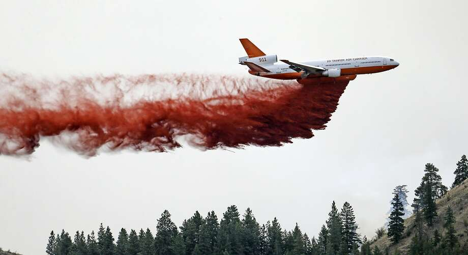 An air tanker drops fire retardant on the huge blaze near the scenic Methow Valley northeast of Seattle. Photo: Elaine Thompson, Associated Press