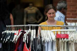 Bridgette Lemoine organizes the items for sale on a rack outside Ann Taylor at the annual New Canaan Village Fair & Sidewalk Sale, New Canaan, CT Saturday, July, 19th, 2014.