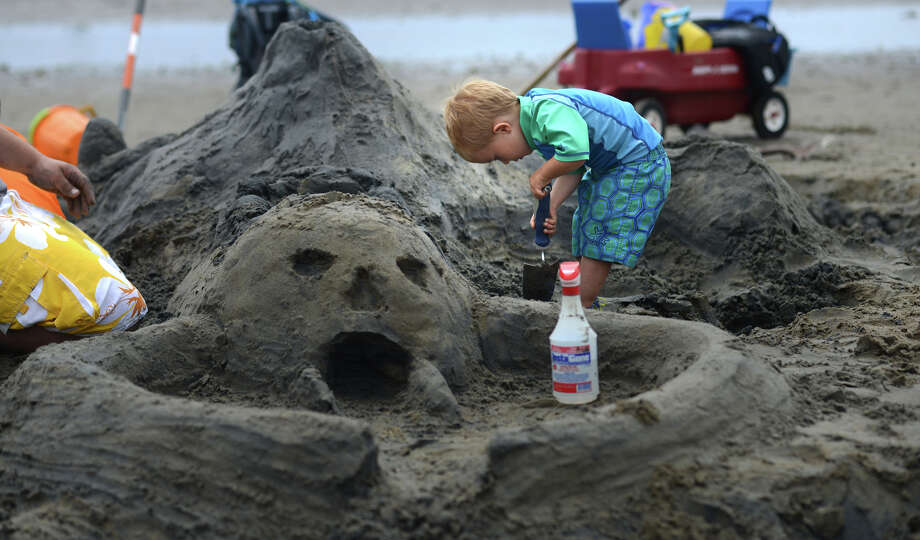 Three-year-old Logan Swett, of Milford, creates a pirate island during the Milford Arts Council's Sand Sculpture Competition Saturday, July 19, 2014, at Walnut Beach in Milford, Conn. Photo: Autumn Driscoll / Connecticut Post