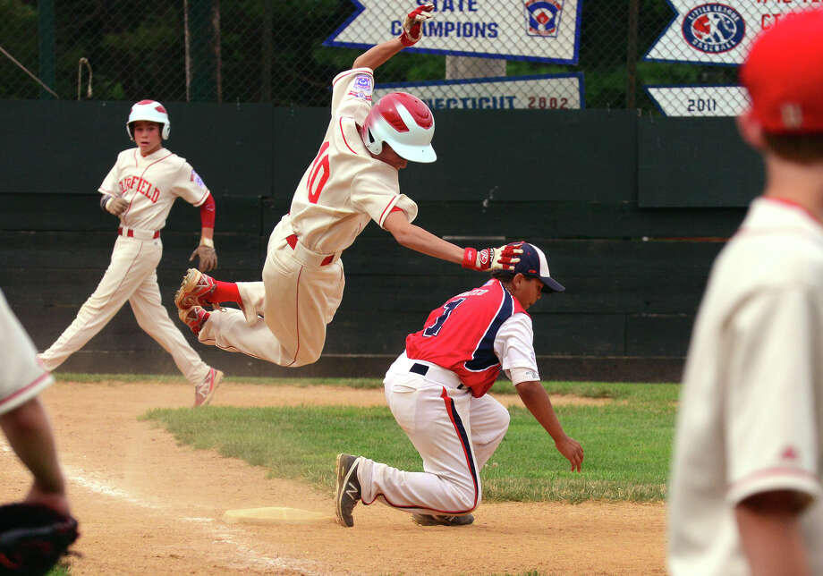 Fairfield American's Sam Davenport flies through the air after tripping while reaching first base, during little league sectional tournament action against Norwalk at Old Tavern Park in Orange, Conn. on Saturday July 19, 2014. Photo: Christian Abraham / Connecticut Post