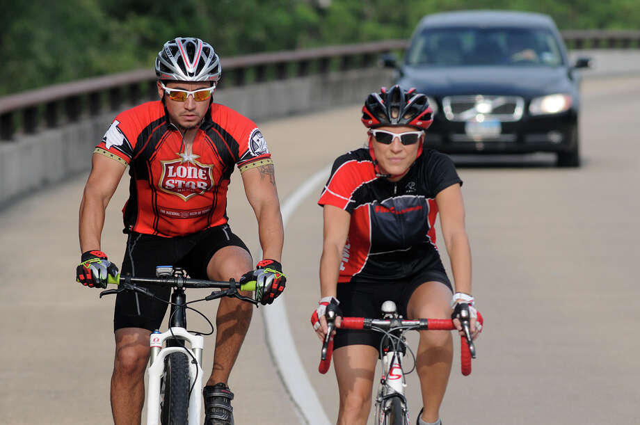 Candice Adams, a member of The Woodlands Cycling Club's board of directors, bikes along Lake Woodlands Parkway on a recent Friday ride with Tim Palacios, left. Photo: Jerry Baker, Freelance