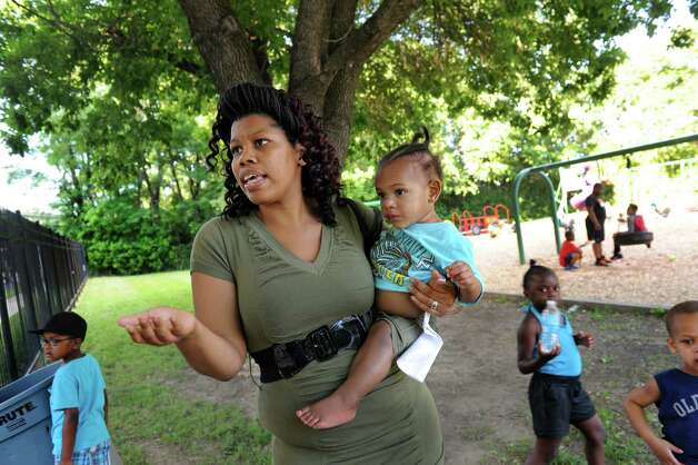 Resident Marquita Nolan holds her nephew Yasir Bullock, 1, as she talks about living next to the rail line that carries oil tankers to the Port of Albany on Thursday, June 19, 2014, at Ezra Prentice Homes in Albany, N.Y. (Cindy Schultz / Times Union) Photo: Cindy Schultz
