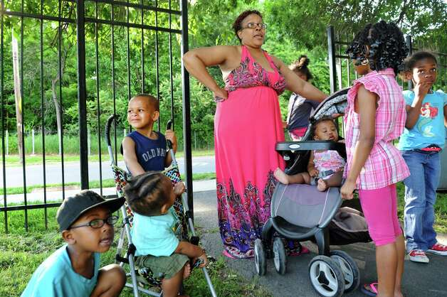 Resident Vanessa Epps, center, is surrounded by neighborhood children as she talks about living next to the rail line that carries oil tankers to the Port of Albany on Thursday, June 19, 2014, at Ezra Prentice Homes in Albany, N.Y. (Cindy Schultz / Times Union) Photo: Cindy Schultz