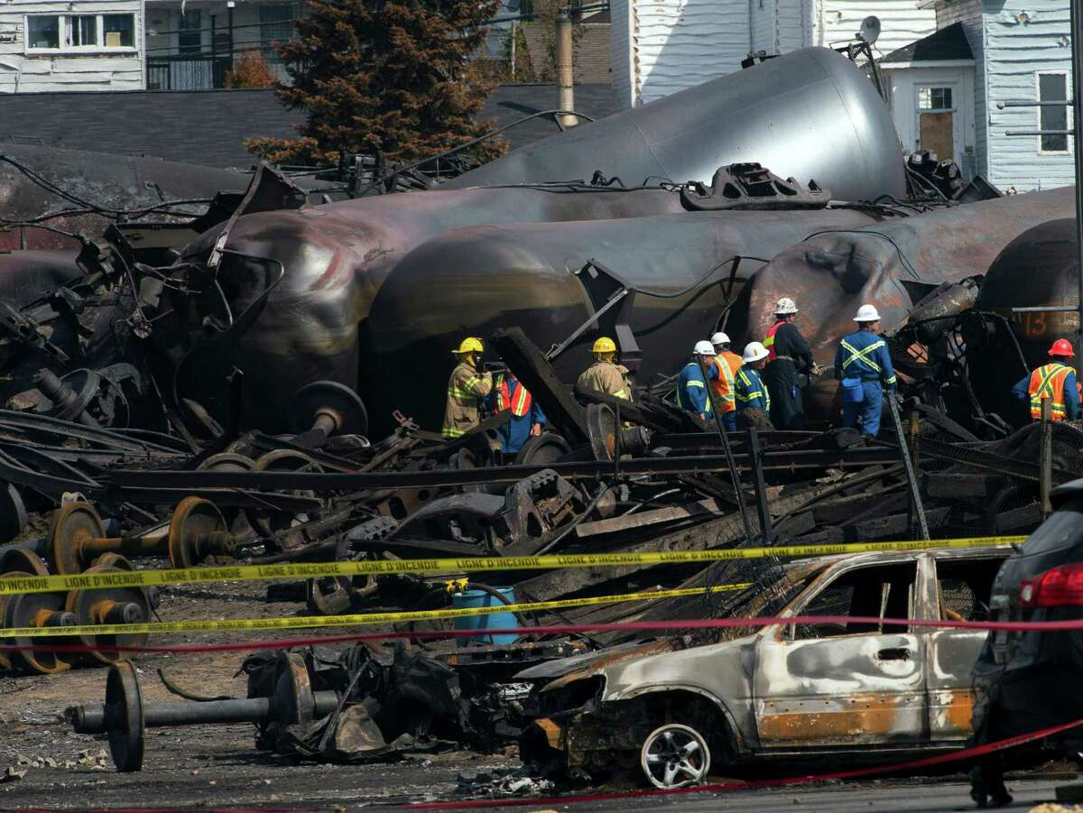 Worker are seen by damaged tanker cars Tuesday, July 16, 2013, as work continues at the crash site of the train derailment and fire in Lac-Megantic, Quebec. The July 6, 2013 derailment left 37 people confirmed dead and another 13 missing and presumed dead. (AP Photo/Ryan Remiorz, Pool) ORG XMIT: RYR112