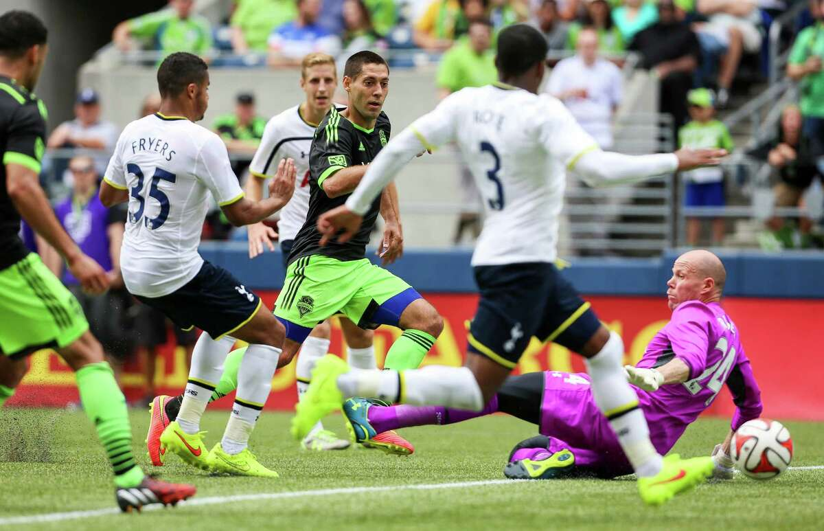 Forward Clint Dempsey watches as the ball passes Tottenham goalkeeper Brad Friedel during a missed shot.