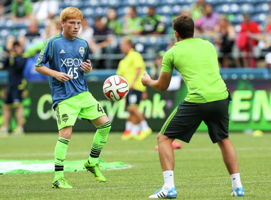 Xander Bailey (left) warms up before the match. Bailey signed with the Sounders before the match as part of a Make-A-Wish Foundation wish. Photo: JOSHUA BESSEX, SEATTLEPI.COM / SEATTLEPI.COM