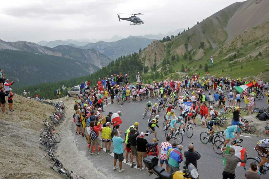 The pack with Italy's Vincenzo Nibali, wearing the overall leader's yellow jersey, climbs Izoard pass during the fourteenth stage of the Tour de France cycling race over 177 kilometers (110 miles) with start in Grenoble and finish in Risoul, France, Saturday, July 19, 2014. (AP Photo/Laurent Cipriani) ORG XMIT: PDJ136 Photo: Laurent Cipriani / AP