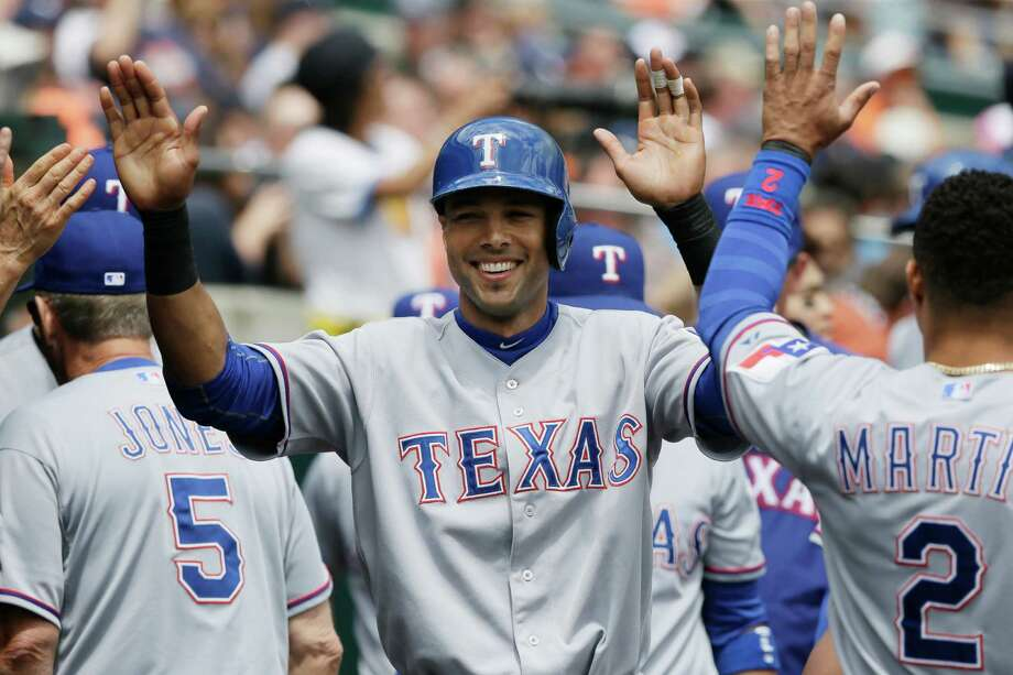 Texas Rangers' Alex Rios high fives teammates after scoring from second on a Chris Gimenez single to right field during the second inning of a baseball game against the Detroit Tigers in Detroit, Thursday, May 22, 2014. (AP Photo/Carlos Osorio) Photo: Carlos Osorio, STF / AP