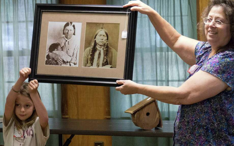 Rachel Cochran, left, and Darlene Elkins holds a picture that was up for auction of Comanche War Chief Quanah Parker and Cynthia Ann Parker during a reunion of the Parker family descendants at Fort Parker State Park on Saturday, July 19, 2014. They are descendants of Elder John Parker and other members of the Pilgrim Predestinarian Baptist Church who immigrated into Texas in 1833. One of those settlers, nine-year-old Cynthia Ann Parker, was kidnapped and grew up among the Comanche people and gave birth to the Comanche War Chief Quanah Parker. Photo: Billy Calzada, San Antonio Express-News / San Antonio Express-News