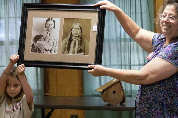 Rachel Cochran, left, and Darlene Elkins holds a picture that was up for auction of Comanche War Chief Quanah Parker and Cynthia Ann Parker during a reunion of the Parker family descendants at Fort Parker State Park on Saturday, July 19, 2014. They are descendants of Elder John Parker and other members of the Pilgrim Predestinarian Baptist Church who immigrated into Texas in 1833. One of those settlers, nine-year-old Cynthia Ann Parker, was kidnapped and grew up among the Comanche people and gave birth to the Comanche War Chief Quanah Parker.