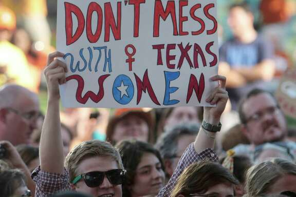A protester holds up a sign during the Planned Parenthood Action Fund's Stand with Texas Women Rally at Discovery Green in Houston in 2013. The rally challenged an abortion restriction bill.